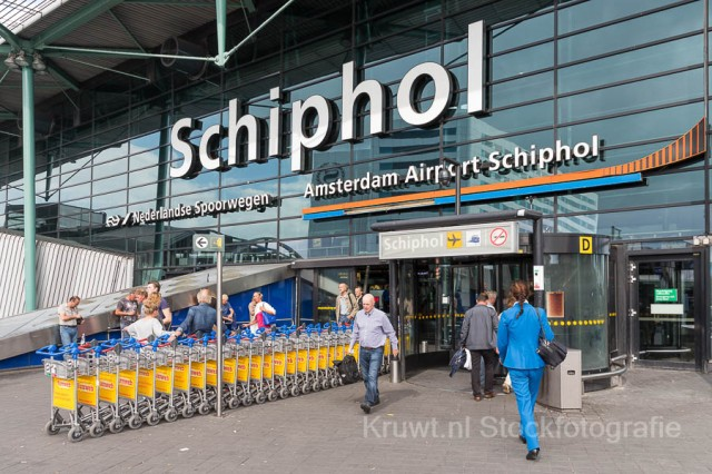 AMSTERDAM, THE NETHERLANDS - SEP 11, 2014: Schiphol Airport entrance with passing travellers and a stewardess